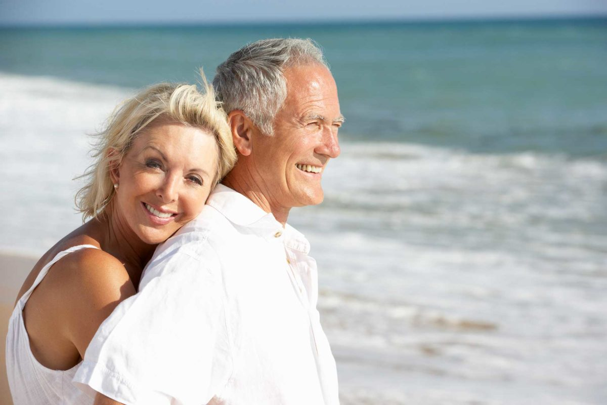husband and wife dental crown patients on beach together