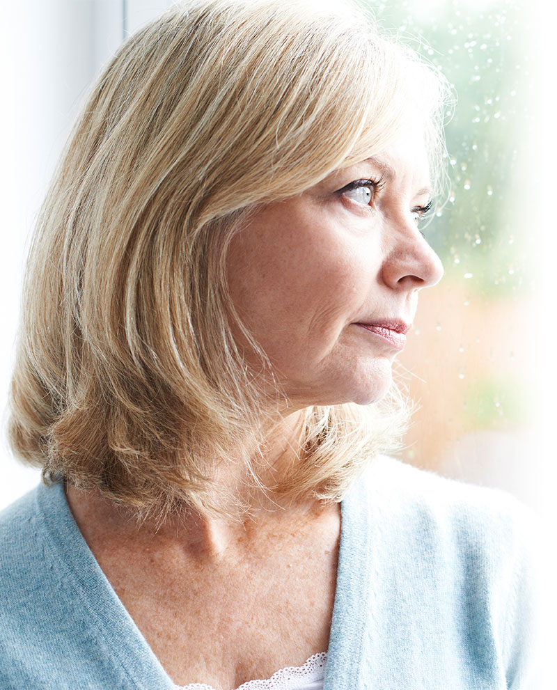 Focused woman staring out window