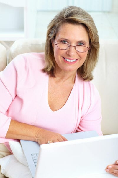 goodyear patient in pink shirt working on laptop